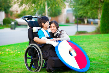 Disabled brother hugging older sister in wheelchair outdoors