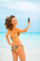 Smiling young woman making selfie on beach