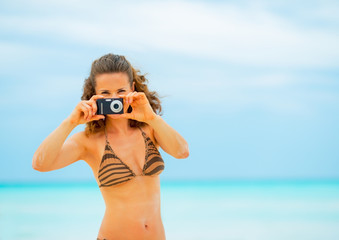 Young woman taking photo while on beach