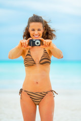 Happy young woman taking photo while on beach