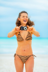 Smiling young woman taking photo while on beach