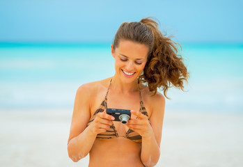 Happy young woman checking photos in camera while on beach