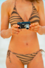 Closeup on young woman checking photos in camera while on beach