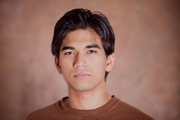 Handsome young man standing against brown background with seriou