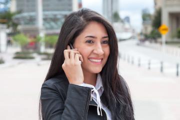Frau mit langen schwarzen Haaren telefoniert in der Stadt