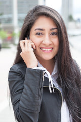 Lachende Frau mit langen schwarzen Haaren und Handy in der Stadt