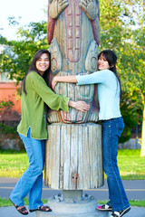 Two young, biracial teen girl in park hugging a totem pole on su