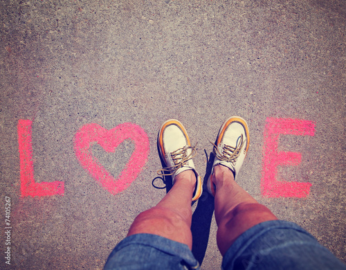 two feet making a sign for the letter V in the word love toned w