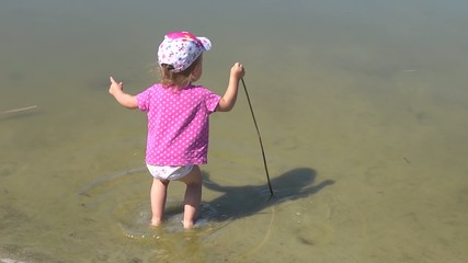 A child girl plays in a pond - carefree childhood