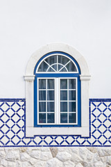 window on a white wall with tiles