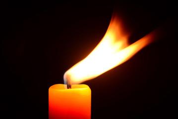 Orange candle burning on a black background
