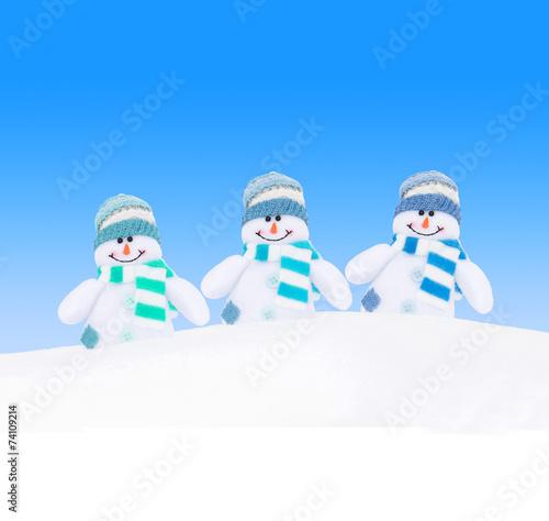 Leinwanddruck Bild Happy winter snowmen family against blue sky