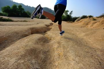 fitness woman legs running on desert trail