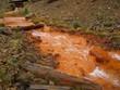 Leinwandbild Motiv Orange pollution from a mine