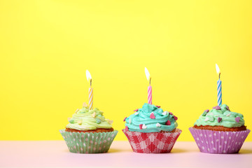 Delicious birthday cupcakes on table on yellow background