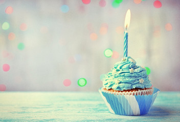 Delicious birthday cupcake on wooden table