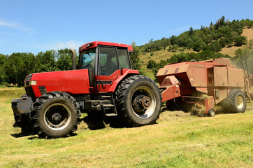 Large Baler working a small farm field of grass hay