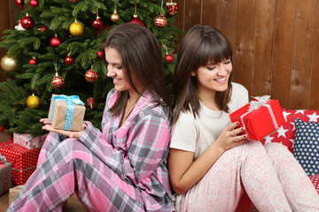 Beautiful girls twins in pajamas near Christmas tree at home