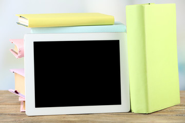 PC tablet and books on wooden table, on light background