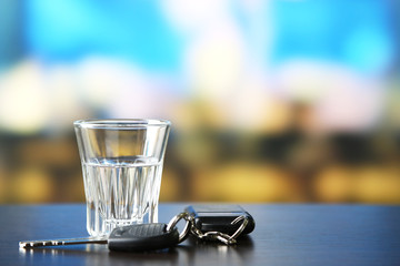 Glass of alcoholic drink and car key,