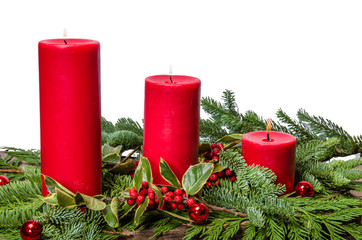 Red candles with cedar boughs and holly