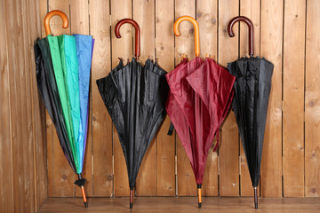 Bright umbrellas leaning against a wooden wall