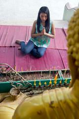 Young woman praying at a statue of Buddha
