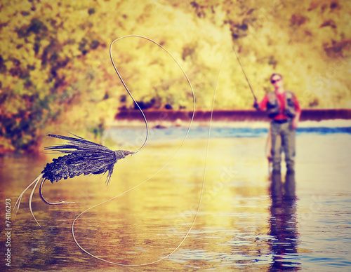 a person fly fishing with a big trout in front - 74116293