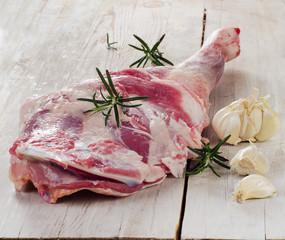 Raw lamb leg on  wooden cutting board.