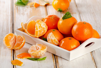 Tangerines with leaves on a  wooden background