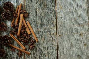 Cinnamon sticks, star anise and pine cones on rustic wood backgr