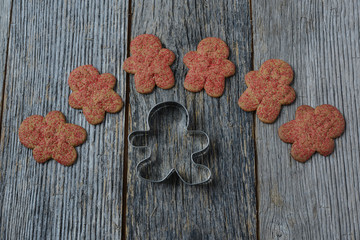Gingerbread Cookie and Cutter on Wood Background