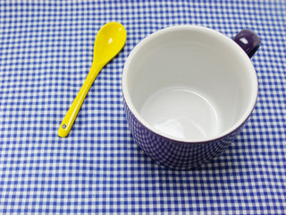 empty ceramic cup and yellow spoon