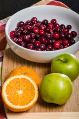 Bowl of cranberries with apples and oranges on board