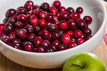 Bowl of cranberries with a green apple