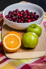 Bowl of cranberries with apples and oranges