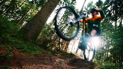 Man on mountain bike jumps in slow motion in woods