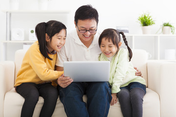 happy father using laptop with little girls