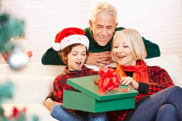 Staunendes Kind öffnet Geschenk zu Weihnachten