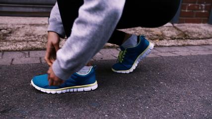 Runner kneels in road and ties shoelaces on shoes