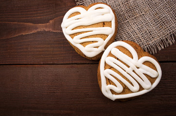 Homemade ginger cookies heart shaped   over wooden table.