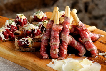 Grissini bread sticks with ham, Cheese,on old wooden background