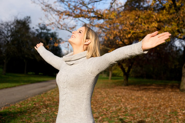 young woman feeling free in a park