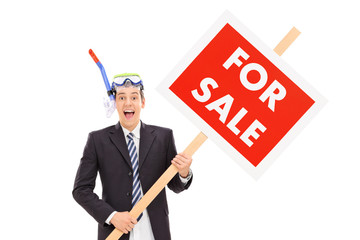 Businessman with snorkel holding for sale sign