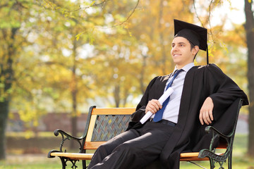 Graduate student holding diploma seated on bench, in park