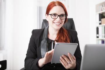 Junge Geschäftsfrau arbeitet im Büro mit einem Tablet Computer