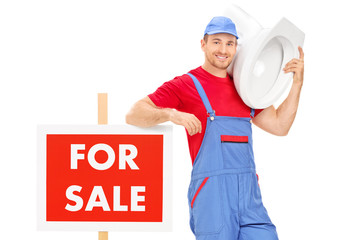 Plumber standing by a for sale sign and carrying a toilet