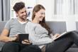 Lachendes Paar auf dem Sofa mit Tablet Computer und  Laptop