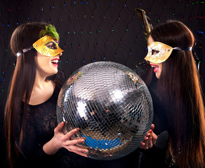 Lesbian women in carnival mask with disco ball.