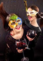 Two sexy lesbian women in carnival mask